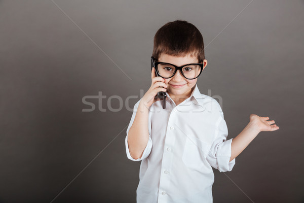 Boy talking on mobile phone and holding copyspace on palm Stock photo © deandrobot
