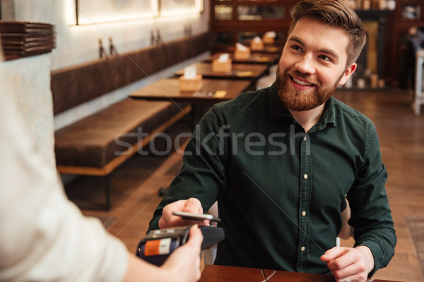 Bearded man sitting in cafe while pays order with phone. Stock photo © deandrobot
