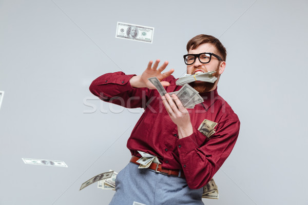 Happy Male nerd playing with money Stock photo © deandrobot