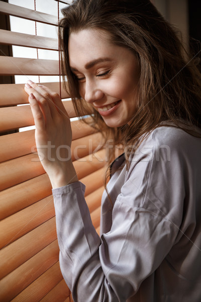 Vertical image of pleased woman standing near the window Stock photo © deandrobot
