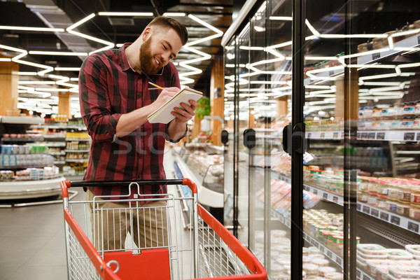 Stock photo: Smiling young man standing in supermarket talking by phone
