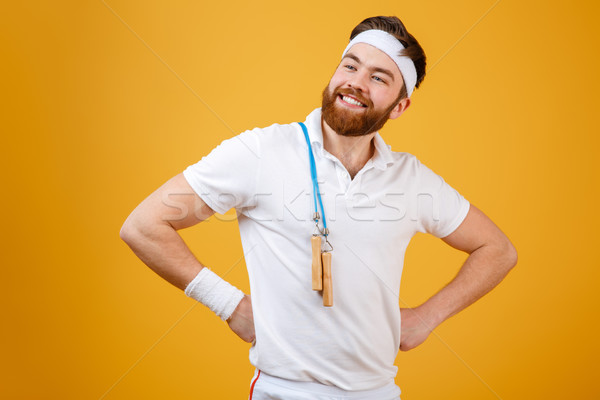 Smiling young sportsman holding skipping rope Stock photo © deandrobot