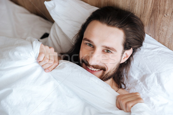 Souriant barbu jeune homme lit maison homme Photo stock © deandrobot