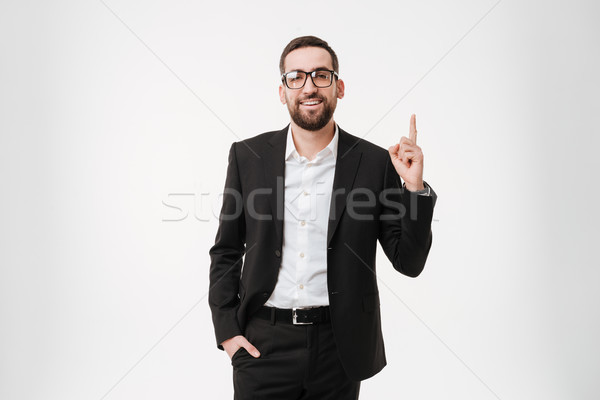Handsome young bearded businessman wearing glasses pointing to copyspace. Stock photo © deandrobot