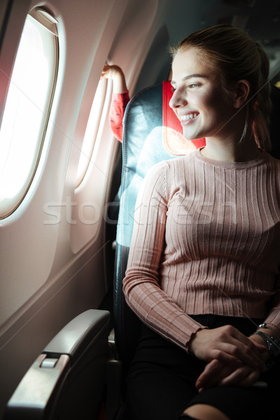 Vertical image of Happy woman in aircraft Stock photo © deandrobot