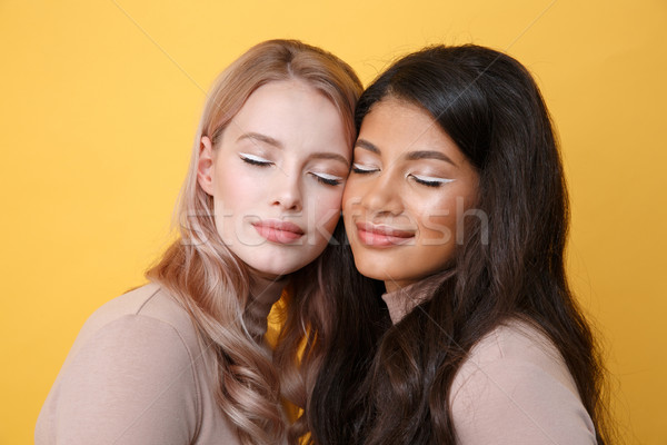 Beautiful young two ladies standing over yellow background Stock photo © deandrobot