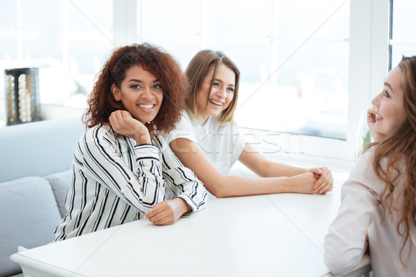 Side view of three women sitting in cafe Stock photo © deandrobot