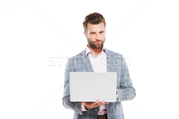 Geconcentreerde jonge man met behulp van laptop computer foto permanente Stockfoto © deandrobot