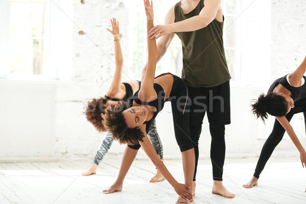 Cropped image of a yoga instructor helping woman to stretch Stock photo © deandrobot