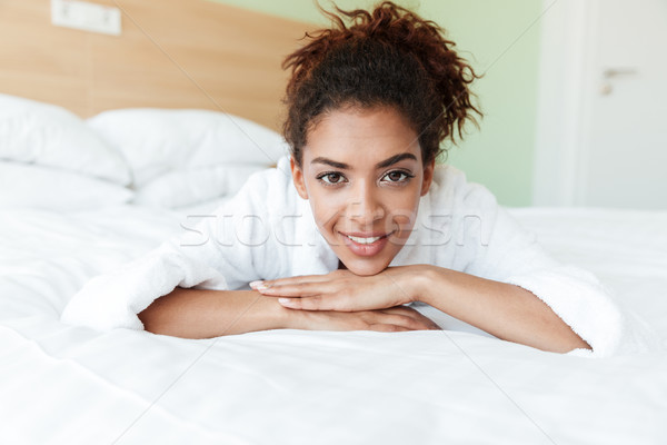 Smiling young african woman lies on bed indoors at home Stock photo © deandrobot