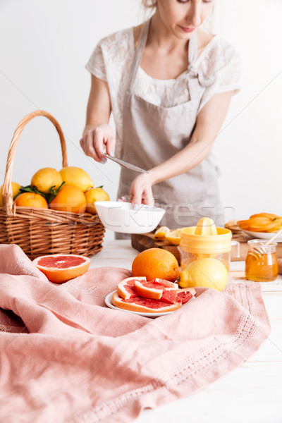 Cropped image of woman squeezes out juice of a citruses. Stock photo © deandrobot
