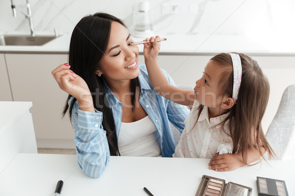 Little asian girl applying make up on her mothers face Stock photo © deandrobot