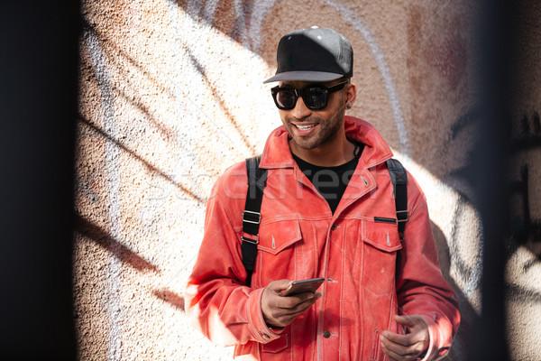 Férfi napszemüveg hallgat zene mobiltelefon fülhallgató Stock fotó © deandrobot