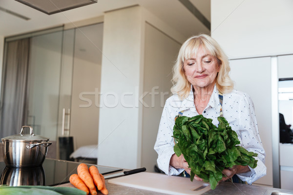 Cheerful mature woman at home cooking in kitchen. Stock photo © deandrobot