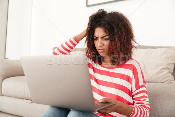 Young displeased upset woman using laptop at home Stock photo © deandrobot