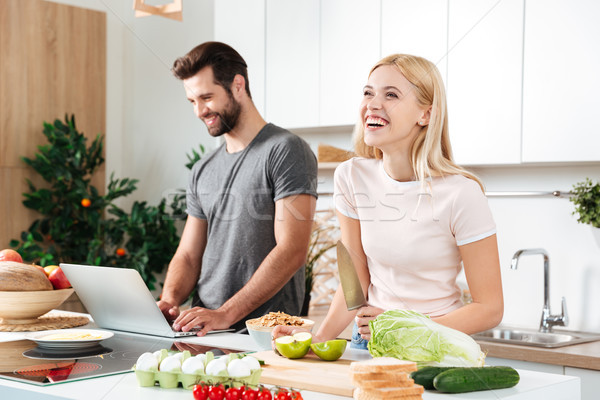 Smiling couple using notebook to cook in their kitchen Stock photo © deandrobot