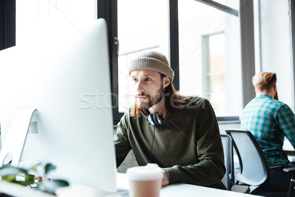 Young handsome man work in office using computer Stock photo © deandrobot