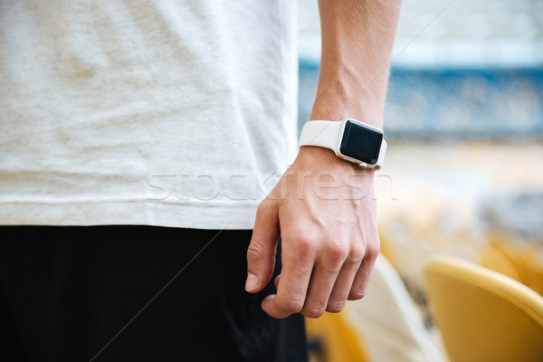 Sportsman's hand with watch at the stadium outdoors. Stock photo © deandrobot