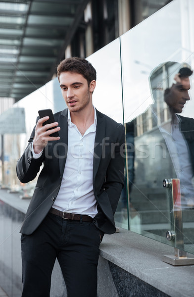 Concentrated young businessman walking near business center Stock photo © deandrobot