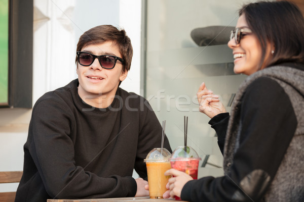Cheerful young lady sitting outdoors with her brother drinking juice Stock photo © deandrobot