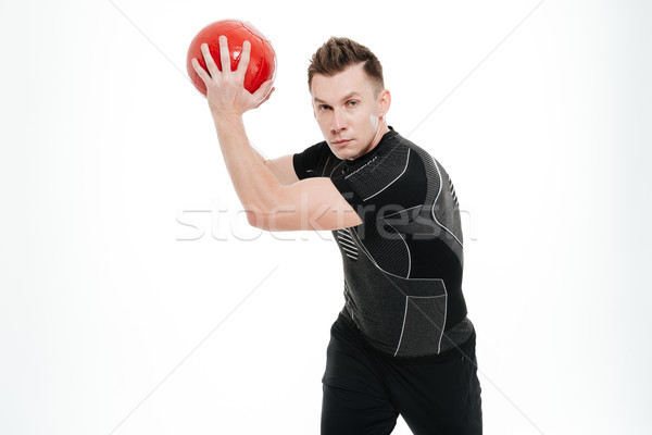 Portrait of a young concentrated sportsman lifting weight fitness ball Stock photo © deandrobot