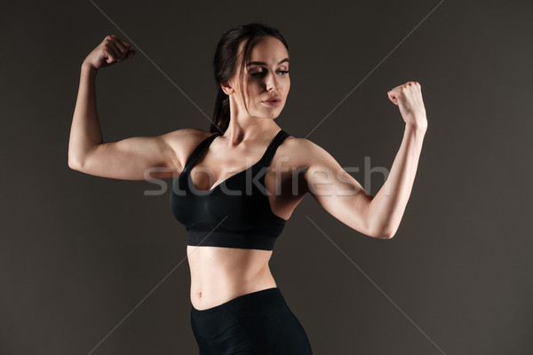 Serious strong sportswoman showing biceps Stock photo © deandrobot
