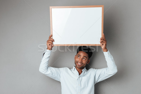 Smiling young african man holding blank board above his head Stock photo © deandrobot