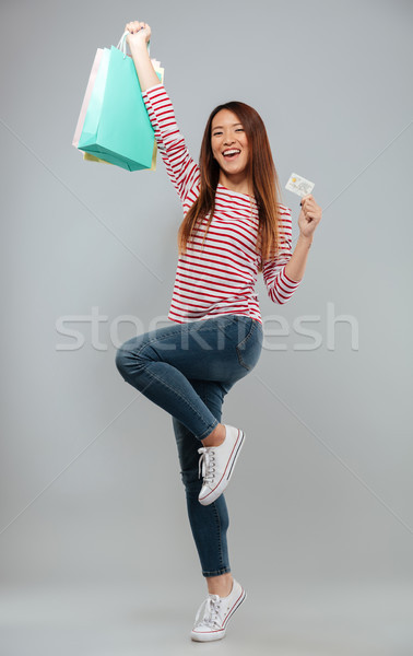 Full length image of Happy asian woman in sweater rejoice Stock photo © deandrobot
