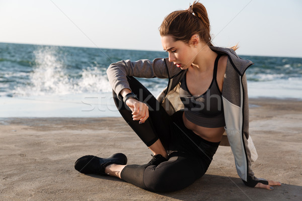 Photo of young beautiful sport woman checking time while sitting Stock photo © deandrobot
