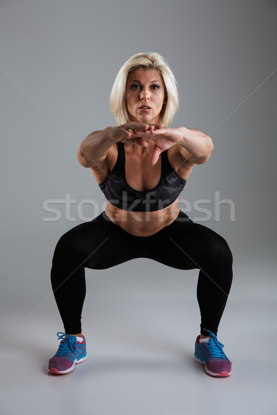 Portrait of a muscular adult sportswoman doing squats Stock photo © deandrobot