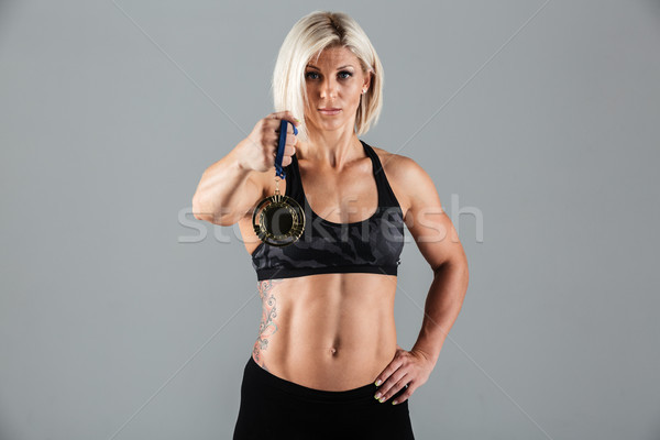 Portrait of a confident athletic sportswoman showing a medal Stock photo © deandrobot