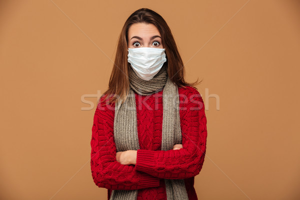 Surprised young woman in protective mask standing with crossed h Stock photo © deandrobot