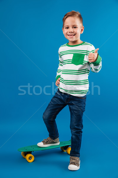 Full length image of pleased young boy posing with skateboard Stock photo © deandrobot