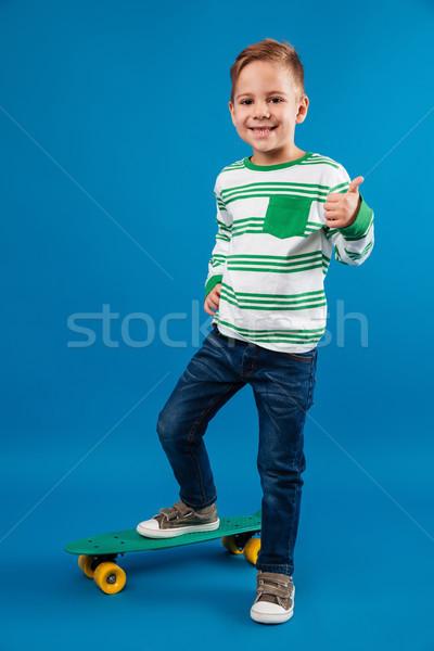 Obraz zadowolony młody chłopak stwarzające deskorolka Zdjęcia stock © deandrobot