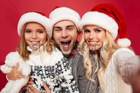 Stock photo: Close-up of young family in Santa's hat having fun while taking