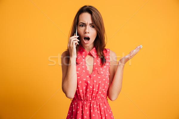Megrémült barna hajú nő ruha beszél okostelefon Stock fotó © deandrobot