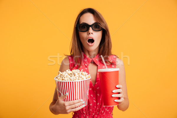 Close-up photo of amazed beautiful young woman in 3d glasses hol Stock photo © deandrobot