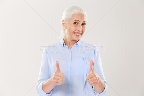 Portrait of cheerful old woman in blue shirt showing thumbs up g Stock photo © deandrobot