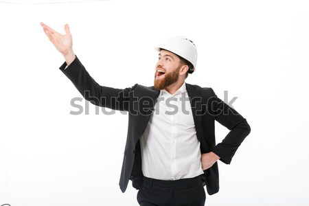 Happy business man in protective helmet pointing and looking away Stock photo © deandrobot