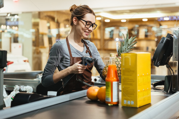 Smiling female cashier scanning grocery items Stock photo © deandrobot
