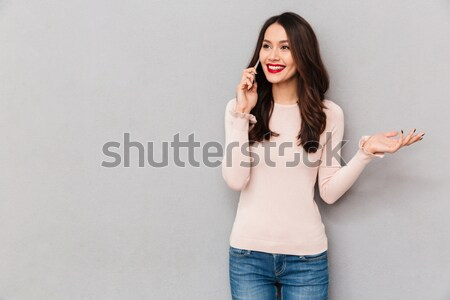 Portrait of pretty smiling woman with brown hair talking on mobi Stock photo © deandrobot