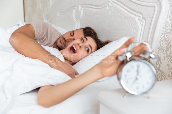 Side view of Surprised Lovely couple sleeping together in bed Stock photo © deandrobot