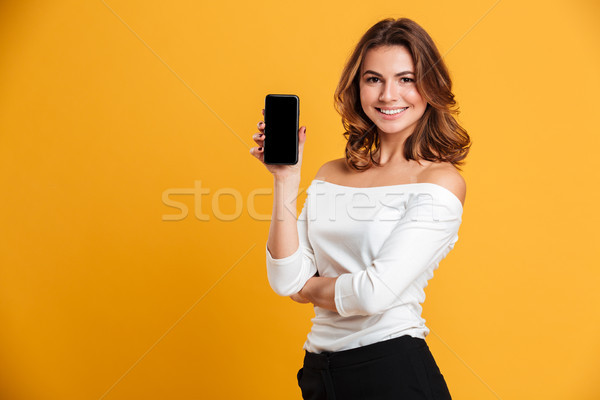 Smiling young woman showing display of mobile phone. Stock photo © deandrobot