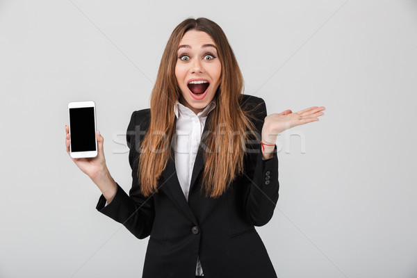 Beautiful lady with opened mouth and showing smartphone with blank screen isolated Stock photo © deandrobot