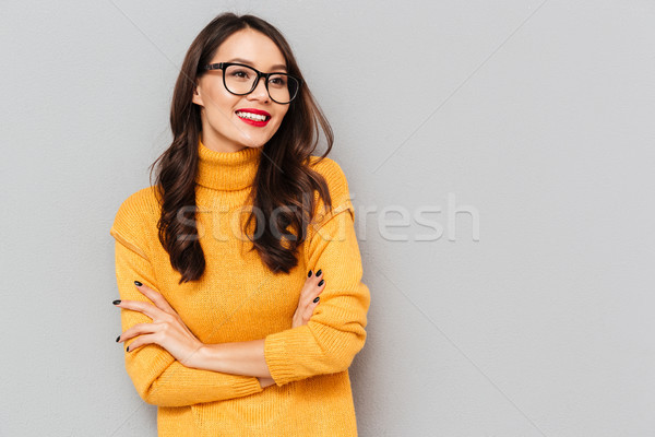 Smiling brunette woman in sweater and eyeglasses with crossed arms Stock photo © deandrobot