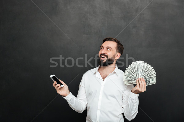 Image of happy man in white shirt winning lots of cash money usi Stock photo © deandrobot