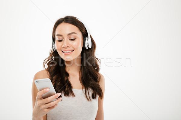 Elégedett barna hajú nő fejhallgató hallgat zene Stock fotó © deandrobot
