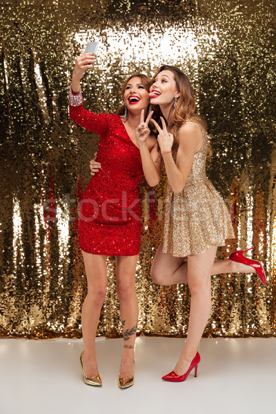 Full length portrait of two funny women in sparkly dresses Stock photo © deandrobot