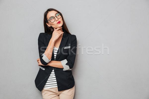 Kép töprengő ázsiai üzletasszony szemüveg felfelé néz Stock fotó © deandrobot