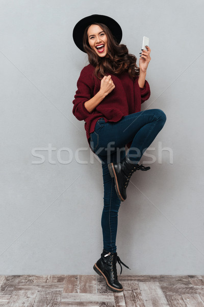 Full length image of cheerful brunette woman in sweater Stock photo © deandrobot